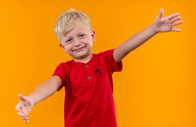 Een vrolijke kleine jongen met blond haar en blauwe ogen die een rood t-shirt draagt en zijn armen wijd opent voor een knuffel terwijl hij op een gele muur kijkt