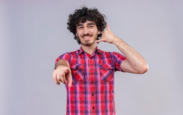 Een vrolijke knappe man met krullend haar in geruit overhemd met hand dichtbij oor, gebaar telefoonteken met vingers