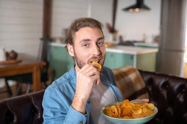 Een vrolijke man die thuis lekkere chips eet