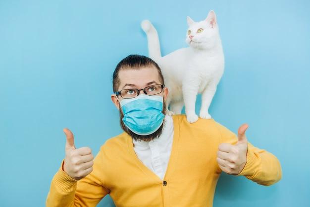 Een vrolijke man in een medisch masker met een witte kat op zijn schouder. pandemie covid 2019. pet.