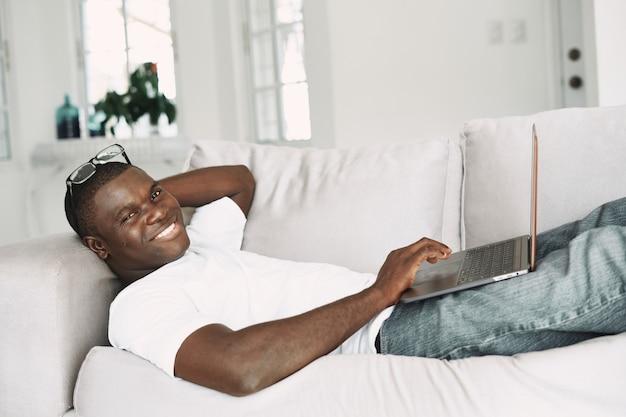 Een vrolijke man met een afrikaans uiterlijk ligt met een laptop op de bank