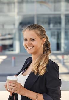 Een vrolijke modieuze vrouw met koffie buitenshuis