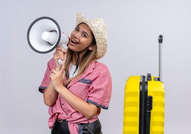 Een vrolijke mooie jonge vrouw die rood overhemd en zonnehoed draagt die door megafoon op een witte muur spreken