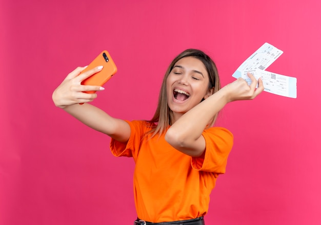 Een vrolijke, mooie jonge vrouw in een oranje t-shirt die lacht en selfie met mobiele telefoon neemt terwijl ze vliegtickets op een roze muur toont