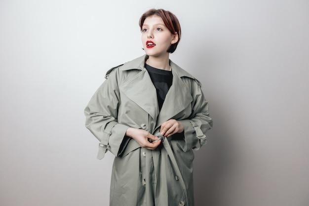 Een vrolijke, mooie vrouw knoopt de riem om haar jas