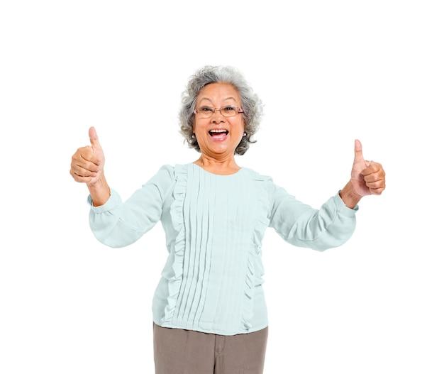 Een vrolijke oude casual vrouw geven duimen omhoog
