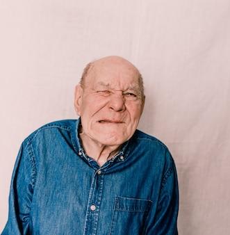 Een vrolijke oude man met rimpels trekt grimassen en trekt gezichten. gekke oude man