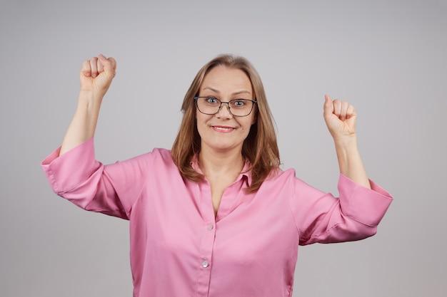 Een vrolijke rijpe vrouw verheugt zich in een succesvol bedrijf. geïsoleerde schot op een grijze achtergrond.