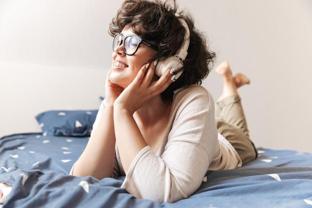 Een vrolijke schattige jonge vrouw ligt binnenshuis op bed luisteren muziek met koptelefoon.