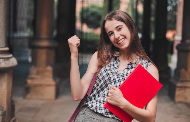 Een vrolijke student met een rood notitieboekje in de buurt van de campus slaagde voor het examen en zei ja