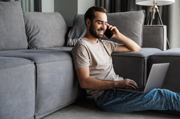 Een vrolijke tevreden jonge man binnenshuis thuis op de bank met behulp van laptopcomputer praten via de mobiele telefoon.