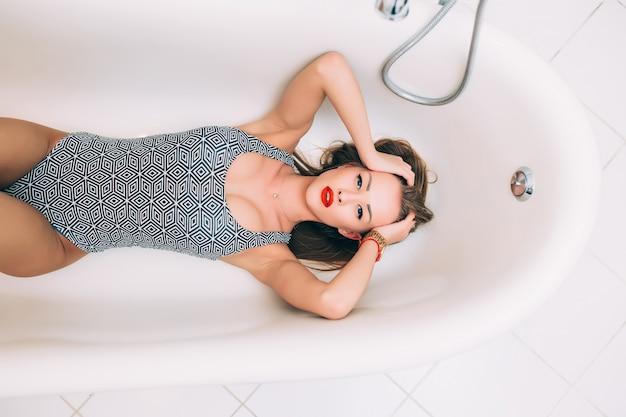 Een vrolijke vrouw ligt in een witte schuimkuip en rust op een schone huid