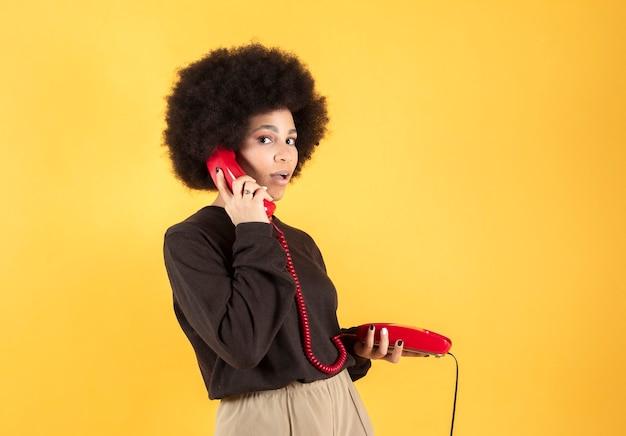 Een vrolijke zwarte vrouw met een speelse glimlach luistert naar een populair liedje via een koptelefoon, houdt een moderne mobiele telefoon vast en luistert graag naar muziek in vrije tijd