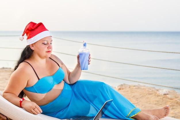 Een vrouw aan de kust in een ligstoel in een pareo-badpak en een kerstman