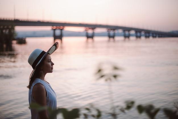 Een vrouw aan zee bij zonsondergang close-up portret in profiel van een bedachtzame vrouw in een strohoed die geniet...