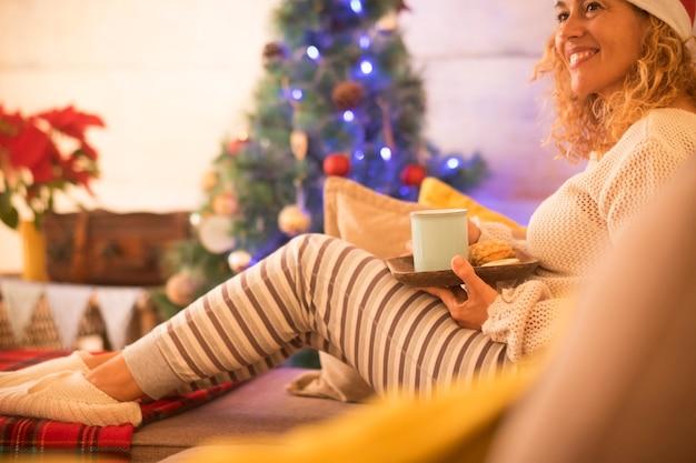 Een vrouw alleen thuis zittend op de bank koekjes etend en thee of koffie drinkend op kerstdag - kerstboom op de achtergrond