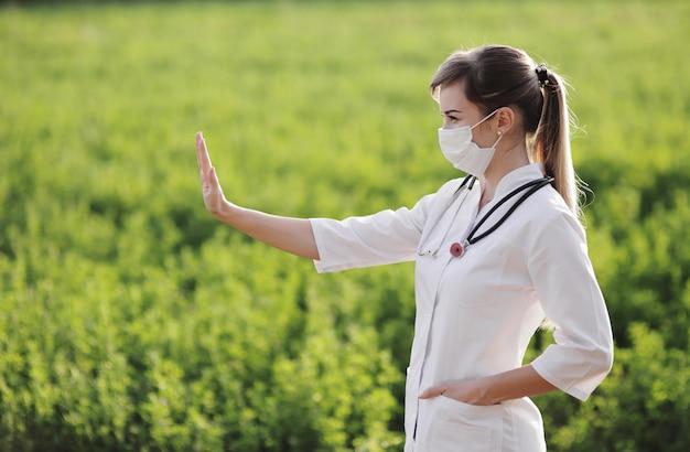 Een vrouw arts in een medisch gezichtsmasker met een einde pandemisch gebaar.