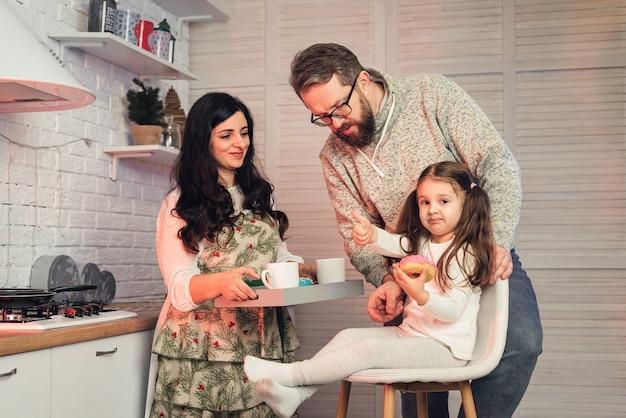 Een vrouw behandelt haar dochter en echtgenoot met thee en donuts