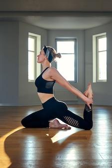 Een vrouw beoefent yoga in een fitnessruimte bij zonsopgang