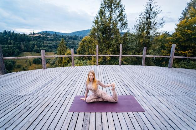 Een vrouw beoefent yoga 's ochtends op een terras in de frisse lucht.