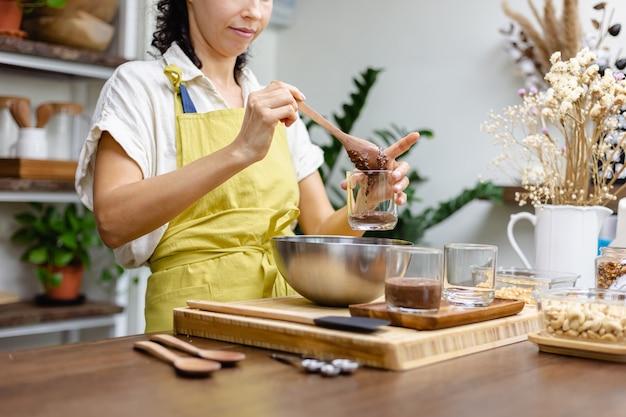 Een vrouw bereidt chia pudding in de keuken en legt de onderste laag amandelmelk, cacao en chiazaadjes klaar.