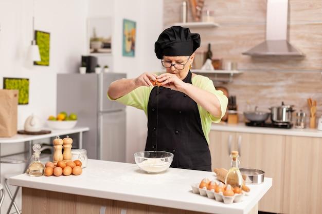 Een vrouw bereidt een deeg voor het bakken van krakende eieren in de thuiskeuken. oudere banketbakker die ei op glazen kom kraakt voor cakerecept in keuken, met de hand mengen, ingrediënten kneden en zelfgemaakte c