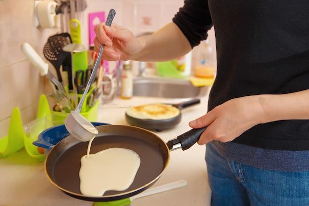 Een vrouw bereidt pannenkoeken, giet het deeg op een hete koekenpan. vakantie maslenitsa.