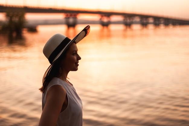 Een vrouw bij de brug over de rivier bij zonsondergang profielportret van een jonge vrouw met een strohoed die toekijkt...