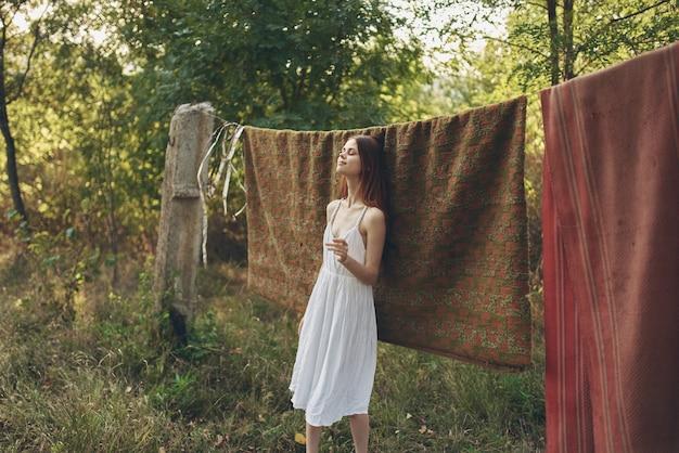 Een vrouw bij de tapijten hing aan een touw buiten in de tuin. hoge kwaliteit foto