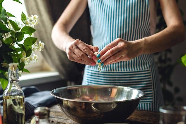 Een vrouw breekt een ei om deeg te maken