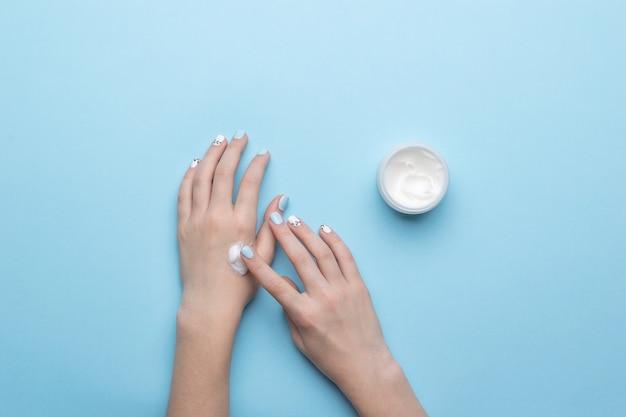 Een vrouw brengt crème uit een potje op haar handen aan op een blauw oppervlak