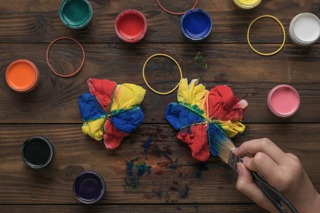 Een vrouw brengt met een penseel verf aan op een set ondergoed in de stijl van tie-dye. stof beitsen in tie-dye-stijl.