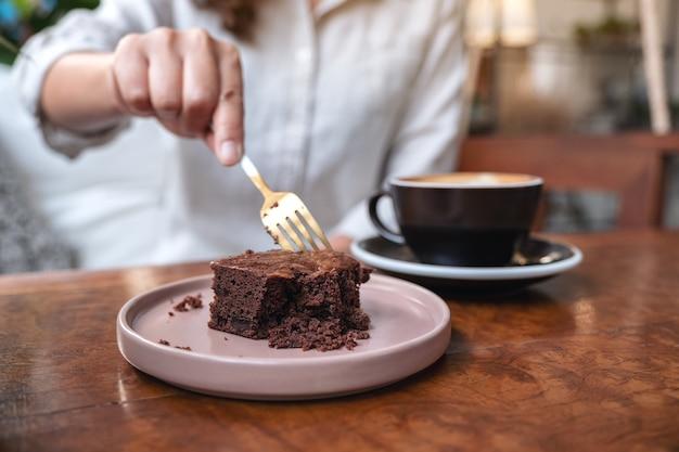 Een vrouw brownie cake met vork met koffiekopje snijden op houten tafel in café