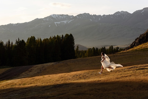 Een vrouw-bruid in een witte trouwjurk loopt in een bergdal met bergen en zonsondergang.