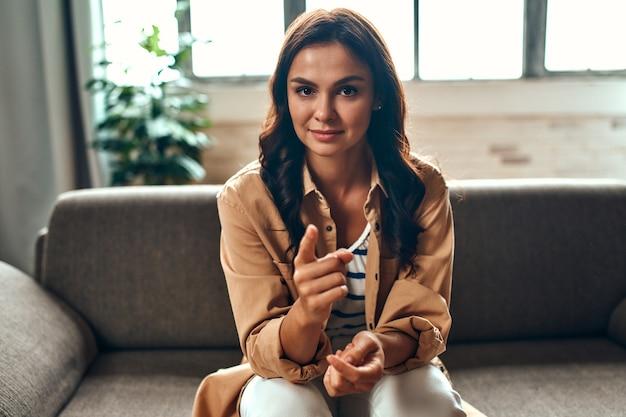 Een vrouw communiceert via een videogesprek terwijl ze thuis op de bank in de woonkamer zit. werk vanuit huis.
