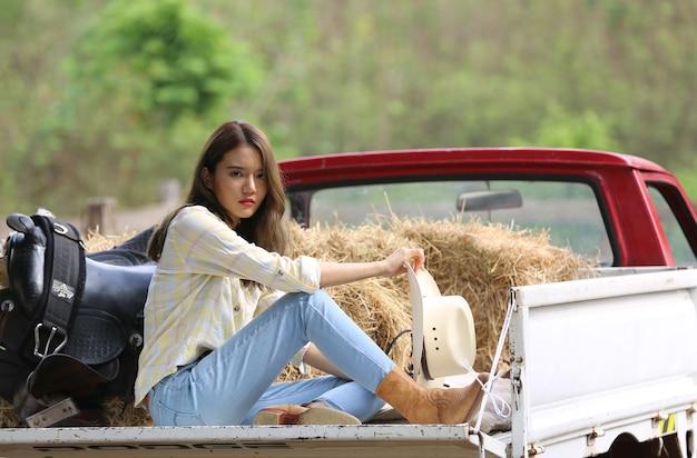 Een vrouw cowgirl outfit kostuum zittend op vrachtwagen tegen paard op een veeboerderij.