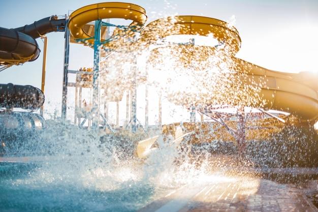 Een vrouw daalde af van een grote, hoge gele glijbaan in een plas helder, helder water en creëerde meer spray