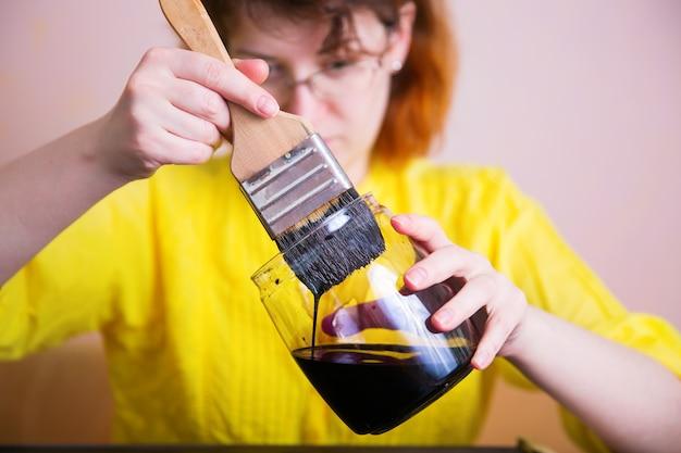 Een vrouw dept een penseel in de donkere verf in de pot