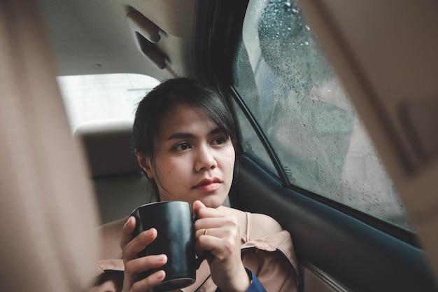 Een vrouw die achter in een auto zit en in een eenzame bui koffie drinkt