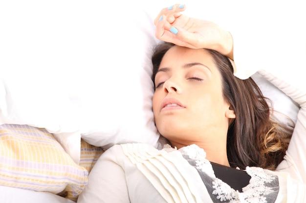 Een vrouw die alleen op het bed ligt.