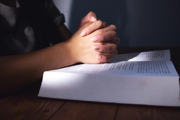 Een vrouw die bidt op een boek