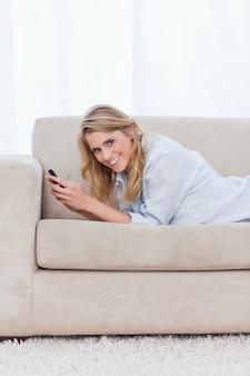 Een vrouw die bij de camera glimlacht houdt een mobiele telefoon