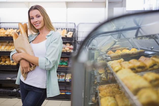 Een vrouw die brood in de gebakjesplank koopt