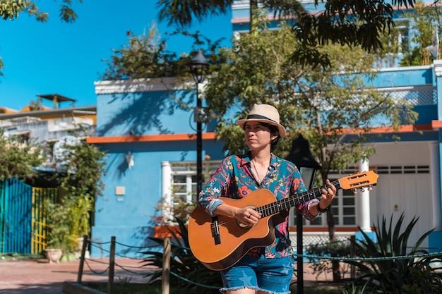 Een vrouw die buiten gitaar speelt
