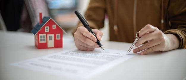 Een vrouw die de overeenkomst van de huislening ondertekent terwijl het houden van huissleutel op witte lijst met huismodel