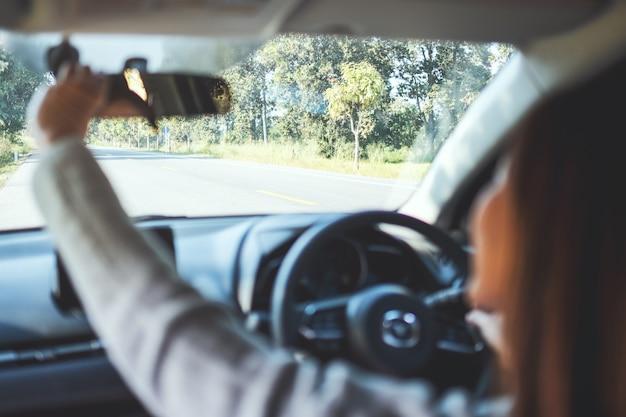 Een vrouw die een achteruitkijkspiegel aanpast tijdens het autorijden
