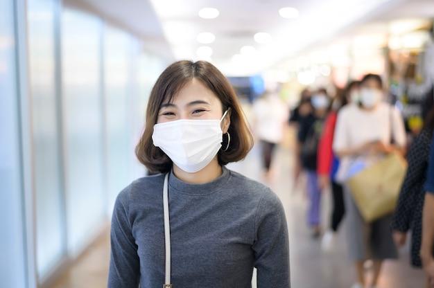Een vrouw die een beschermend masker draagt, winkelt onder covid-19 pandemie in een winkelcentrum, sociaal afstandsprotocol, nieuw normaal concept.