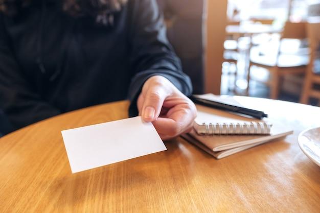 Een vrouw die een blanco, leeg visitekaartje vasthoudt en geeft aan iemand met notitieboekjes op houten tafel