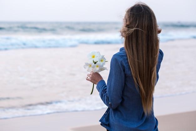 Een vrouw die een bloem houdt