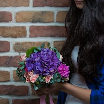 Een vrouw die een boeket van paarse bloemen in de hand houdt